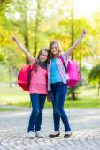 Happy teenage schoolgirls with schoolbag — Stockfoto