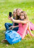 Teenage girls sitting on grass and taking selfie — Stock Photo