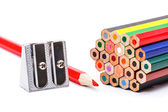Pencil sharpener next to colorful crayons — Stock Photo