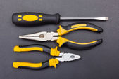 Pliers and screwdriver on black — Stock fotografie