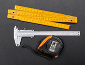 Measuring tools on black: ruler, caliper and tape — Stockfoto