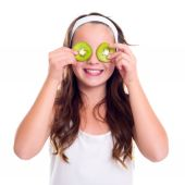 Girl with kiwi slices over her eyes — Stock Photo