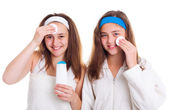 Girls cleaning theirs face with tonic lotion — Stock Photo