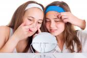 Girls searching for blemishes on theirs skin — Stock Photo