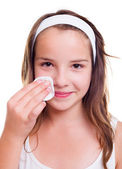 Girl cleaning her face with cotton pad — Stock Photo