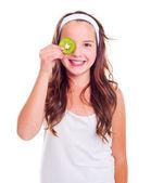 Girl with kiwi slice over her eye — Stock Photo