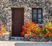 Greek stone house with geranium flowers — Stock Photo