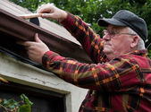 Senior male cleaning out gutter outside house — Stock Photo