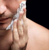 Young man applying a shaving foam — Stock Photo
