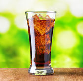 Glass of cola with ice on nature background — Stock Photo