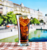 Glass of cola with ice on a table in cafe — Stock Photo