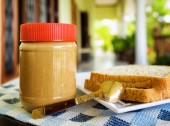 Jar of peanut butter and toasts on summer terrace — Stock Photo
