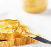 Jar of peanut butter and toasts on white table — Stock Photo