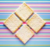 Yellow biscuits on striped background — Foto Stock