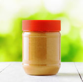 Jar of peanut butter on nature background — Stock Photo