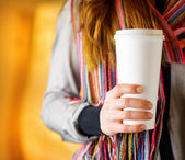 Young woman holding a tumbler of coffee in cafe — Stock Photo