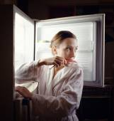 Young woman looking for some snack in fridge late at night — Stock Photo