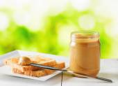 Jar of peanut butter and toasts on nature background — Stock Photo