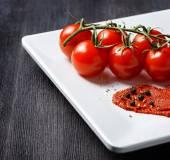 Pasta de tomate y tomates maduros en un plato blanco en un tabl madera — Foto de Stock