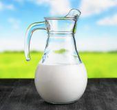 Jug of organic milk on meadow background — Stok fotoğraf