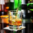 Постер, плакат: Whiskey pouring from a bottle into a glass in a bar