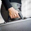 Business woman holding an aluminum briefcase — Stock Photo #66127463