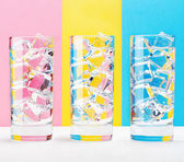 Three glasses on colorful background. — Stock Photo