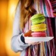 Young woman holding the french pastry macaron in cafe — Stock Photo #66450255