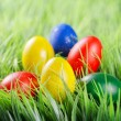 Colorful Easter eggs lying in a pyramid shape on green grass in — Stock Photo #67673297