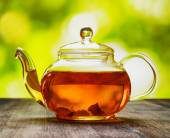 Glass teapot of fresh aromatic tea on a wooden table and on natu — Stock Photo
