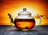 Glass teapot of fresh aromatic tea on a black wooden table and o — Stock Photo