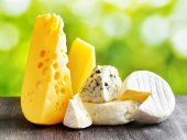 Different types of cheese on a black wooden table and on nature  — Stock Photo