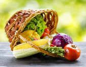 Fresh vegetables falling out of an inverted basket on black wood — Stock Photo