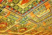 Gilded red patterns on the ceiling in interior of the Po Lin Mon — Stock Photo