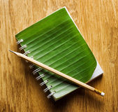 Notebook binding in green banana leaf on wooden board and a penc — Stock Photo