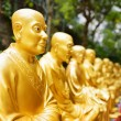 Golden Buddha statues and landscape with green trees — Stock Photo #69099657