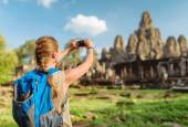 Female tourist taking picture of Bayon temple. Angkor, Cambodia — Stock Photo