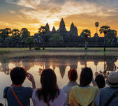 Asian tourists taking picture of Angkor Wat at sunrise — Stock Photo