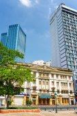 Ho Chi Minh, Wietnam - 30 kwietnia 2015: Kontrast nowoczesnej i architektury budynków w samym sercu miasta Ho Chi Minh. Hotele na tle błękitnego nieba. Ho Chi Minh jest popularnym ośrodkiem turystycznym w Azji. — Zdjęcie stockowe