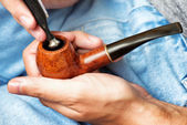 Man holding smoking pipe in hand and tamping down tobacco — Stockfoto