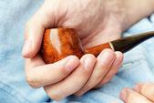 Man holding smoking pipe in hand. Closeup — Stockfoto