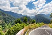 Bend of road and a view of the mountains around Da Lat city (Dalat) on beautiful sky background in Vietnam — Stock Photo