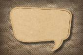 Cardboard speech bubble on burlap background — Stock Photo