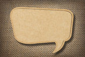 Cardboard speech bubble on burlap background — Stockfoto