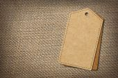 Background of burlap hessian sacking with blank paper tag — Stock Photo
