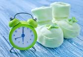 Clock and baby socks — Stock Photo