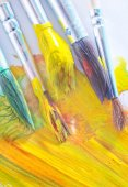 Brushes in yellow paint — Stock Photo