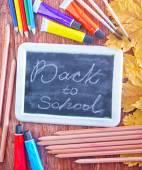 Chalkboard, school supplies and autumn leaves — Stock fotografie