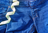 Jeans and green measuring tape — Stock Photo