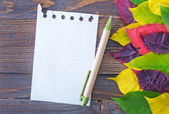 Yellow leaves and notepad — Stock Photo